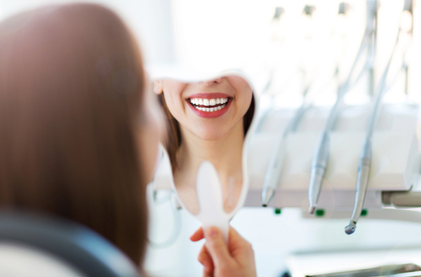 Woman looking at her smile in a mirror in Lilburn, GA
