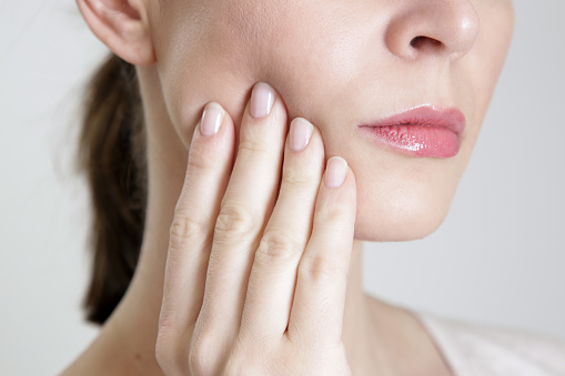 Woman pressing her aching jaw